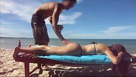 Casal amador exibicionista na praia tomando bronze