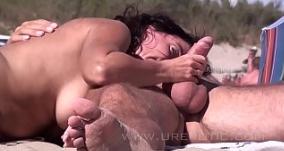 Mulher pagando boquete no flagras na praia de nudismo